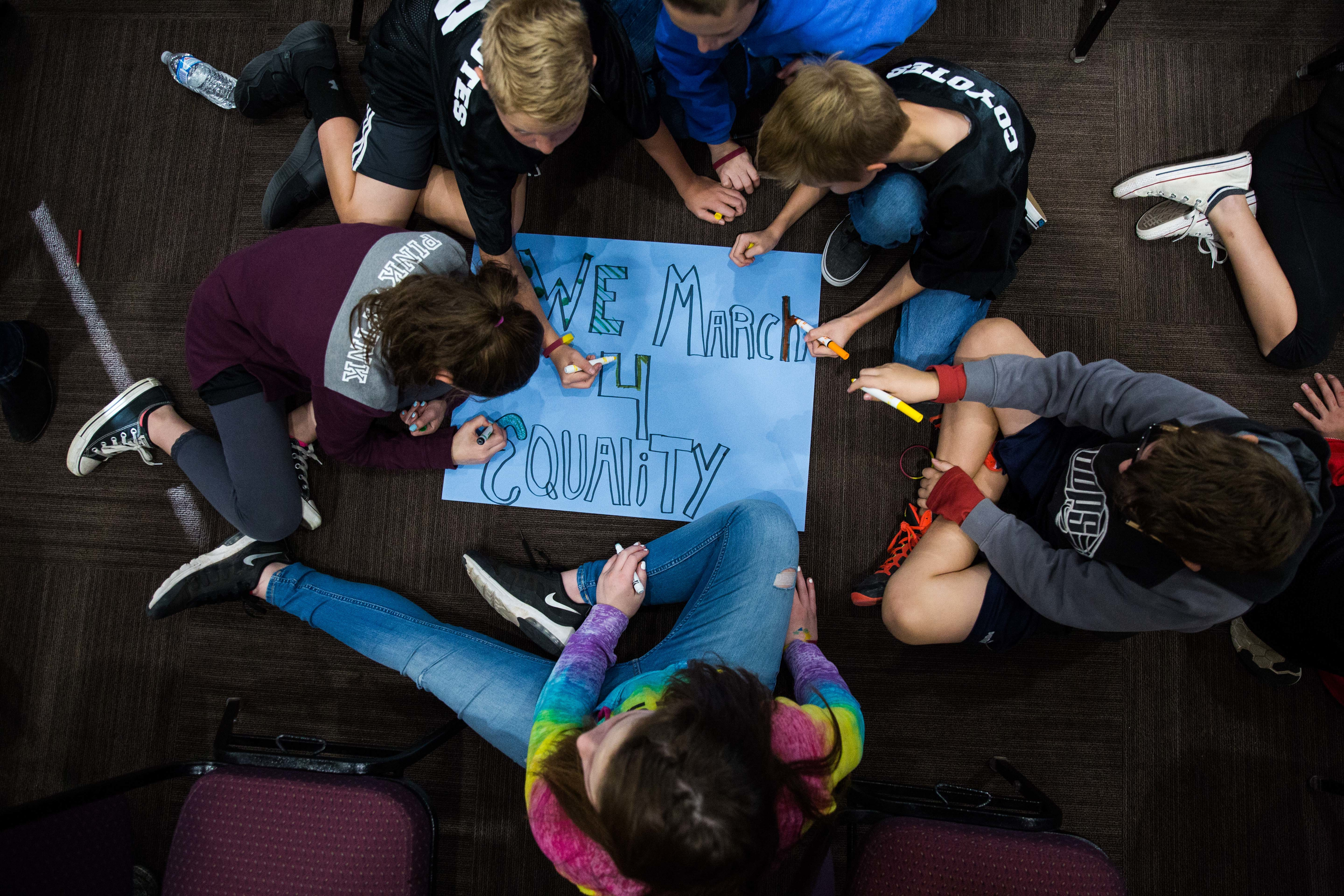 A group of students sitting on the floor working on a poster that says We March 4 Equality
